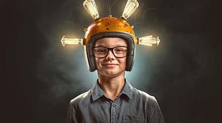 kid in glasses wearing a lightbulb helmet