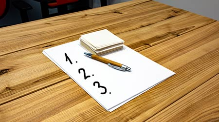 The list 1 2 3 on white paper sheets and notes for writing together with a ballpoint pen lie on a wooden table.