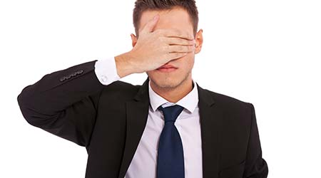 Young man in a suite covering his eyes