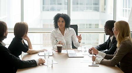Female boss leading a corporate meeting of workers of various races