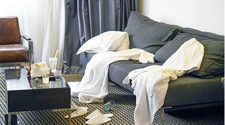Mess in the hotel room. Scattered bathrobes and dirty and the table with the remnants of food and plastic cups.