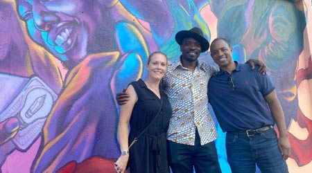 Artists stand in front of Lysol Commissioned COVID-19 Vaccine Awareness Murals