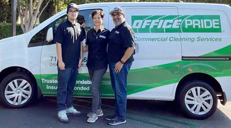 a married couple with their son standing in front of a work van