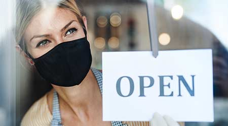 Coffee shop woman owner with face mask, open after lockdown quarantine.  H
