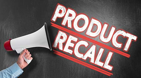 hand holding megaphone or bullhorn against blackboard with text PRODUCT RECALL