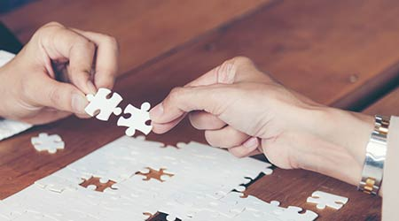 Business people team work holding two jigsaw connecting couple puzzle piece for matching to goals target, success and start up new project in office.