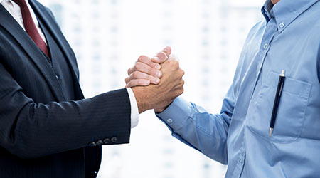 Business people shake hands when reaching a business agreement together.