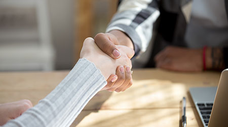 people shaking hands at an office desk