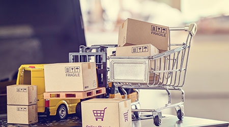 Logistics, supply chain and delivery service for e-commerce, online shopping concept : Boxes, shopping cart, fork-lift truck, delivery van on a laptop computer, depicts using internet to order goods