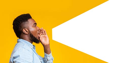 man making loud announcement at copy space, holding hand near his open mouth over yellow background, side view