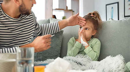 Father taking care of his daughter ill with flu at home