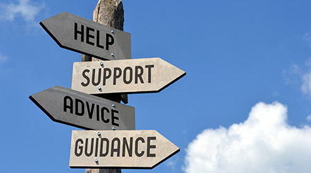 """A wooden post with four arrows pointing in different direction. They read: """"Help"""" """"Support"""" """"Advice"""" """"Guidance"""""""