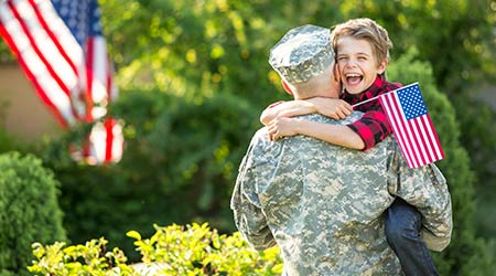A boy jumps in the arms of his father who has returned from active duty