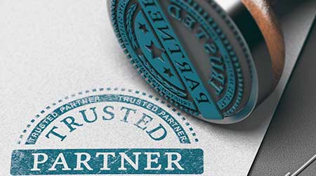 Trusted partner mark imprinted on a paper background with rubber stamp. Concept of trust in business and partnership