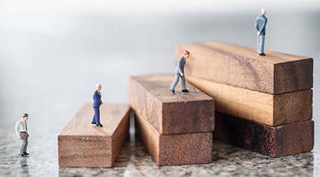 Plastic figures placed on building blocks to symbolize climbing up the corporate ladder