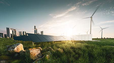 Concept of sustainable energy solution in beautifull sunset backlight. Frameless solar panels, battery energy storage facility, wind turbines and big city with skyscrapers in background.