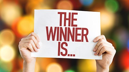 """""""The Winner Is..."""" written in red text on a white piece of paper"""