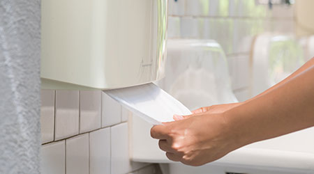 Woman pulling paper towel from dispenser in restroom