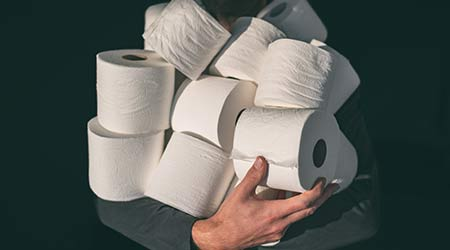 Toilet paper shortage coronavirus panic buying man hoarding carrying many rolls at home in fear of corona virus outbreak closing shopping stores.  M