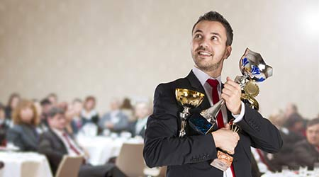 Geeky business guy in a suit holding a few awards that he won at a ceremony