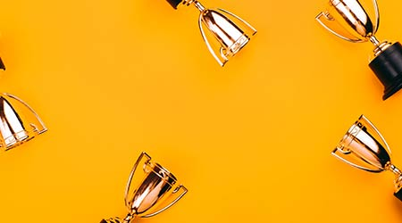 a bunch of trophies against a bright background