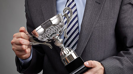 Businessman celebrating with trophy award for success in business or first place sporting championship win