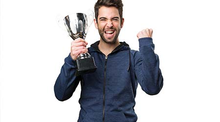 young man holding a trophy and doing winner gesture