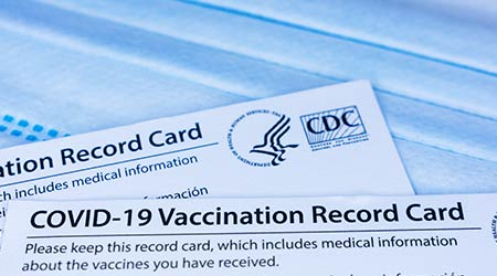 Closeup. Covid-19 vaccination record cards issued by CDC, United States Centers for Disease Control and Prevention, on a blue disposable face mask - San Jose, California, USA - 2021