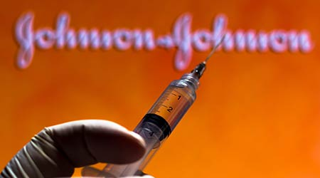 syringe being held by a gloved hand in front of the Johnson & Johnson logo