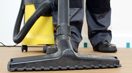 Craftsman at construction site during renovation with industrial vacuum cleaner while vacuuming