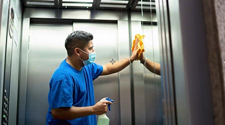 latino janitor cleaning an elevator