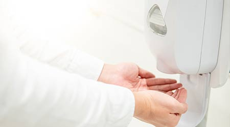 Male patient hands using automatic alcohol dispenser for cleaning hand in the hospital. Infection prevention concept.