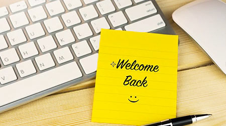 """""""Welcome back"""" with smiley face written on a note placed on a Mac keyboard in an office."""