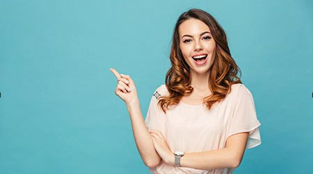 Image of happy young lady standing isolated over blue background.