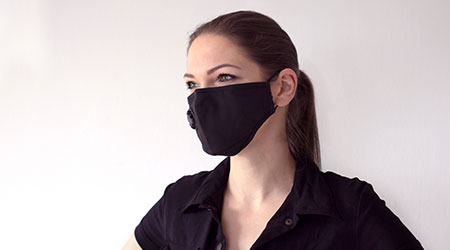 COVID-19 Pandemic Coronavirus. A young woman on a light background in a protective mask to stop spread of the SARS-CoV-2 disease virus.