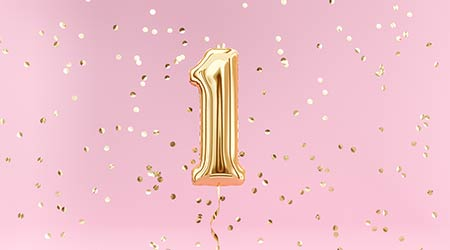 A gold balloon on a pink background to celebrate one year