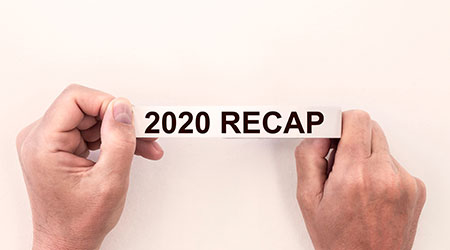 2020 recap inscription text on a white tape in male hands isolated on a white background
