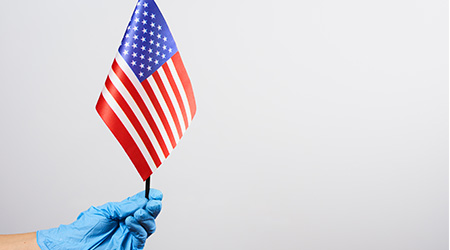 American health care system worker or doctor in surgical gloves holding national flag of United States of America. Symbol of victory over coronavirus or covid-19 disease