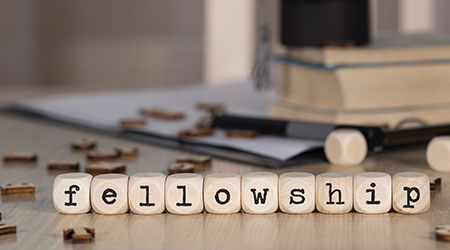 Word FELLOWSHIP composed of wooden dices. Black graduate hat and books in the background. Closeup