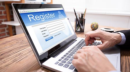 Businessman's Hand Filing Online Registration Form On Laptop