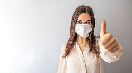 caucasian young woman with disposable face mask. Protection versus viruses and infection. Studio portrait, concept with white background. Woman showing thumb up.