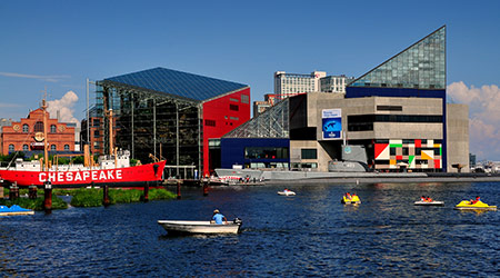 Small boats ply the waters at Inner Harbor in front of the ultra-modern National Aquarium and the Lightship Chesapeake
