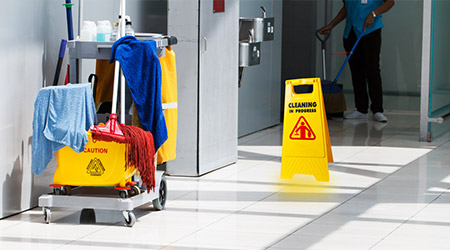 janitorial mop bucket on cleaning in process and worker background