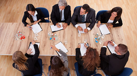 Overhead view of a group of professional business people in a meeting seated around a wooden table with their notepads