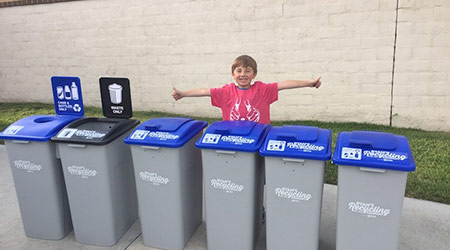 Ryan Hickman of Ryan's Recycling stands in front of various recycling containers