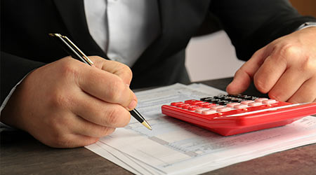 man sitting at table with calculator, document and pen.