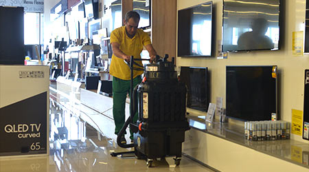 Man pushes walk-behind floor equipment to clean and shine the floors inside a retail store