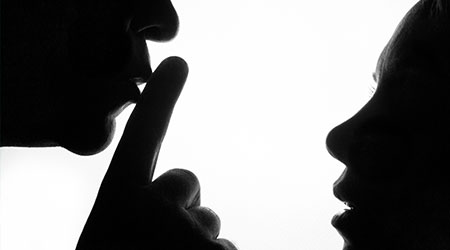 Man holding finger in front of his mouth to signal woman not to say anything