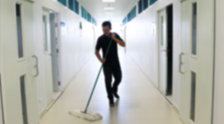 Asian janitor man mopping floor in office building or walkway school