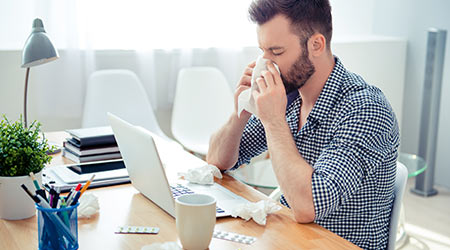 businessman having cold in the head and sitting at workplace